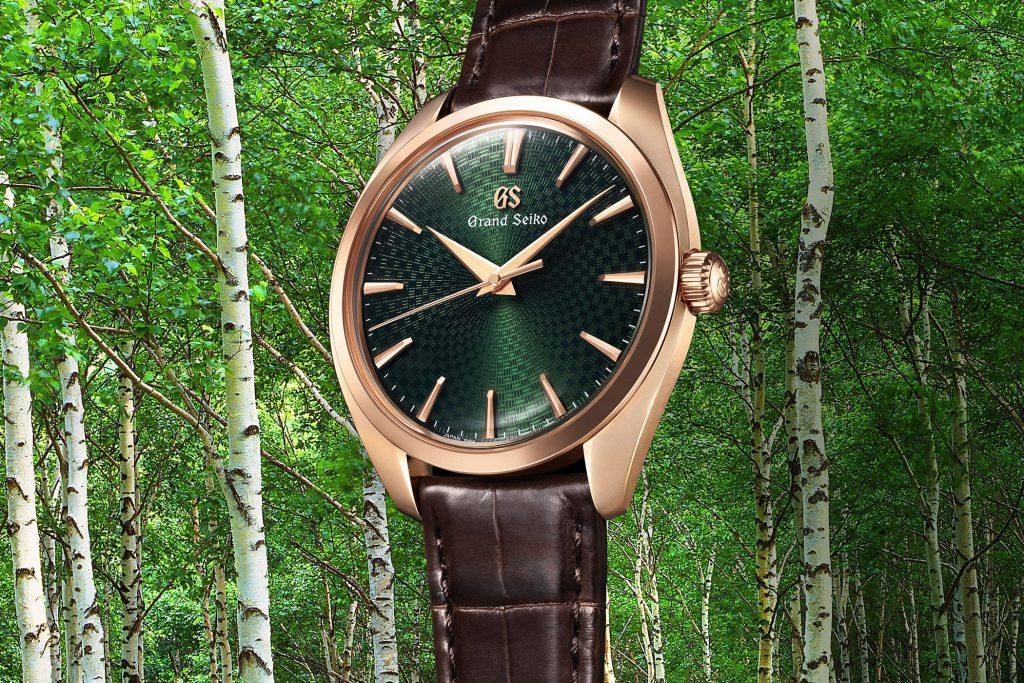 שעון SBGW264 עם לוח ירוק על רקע עצי השדר. מקור - Monochrome Watches.