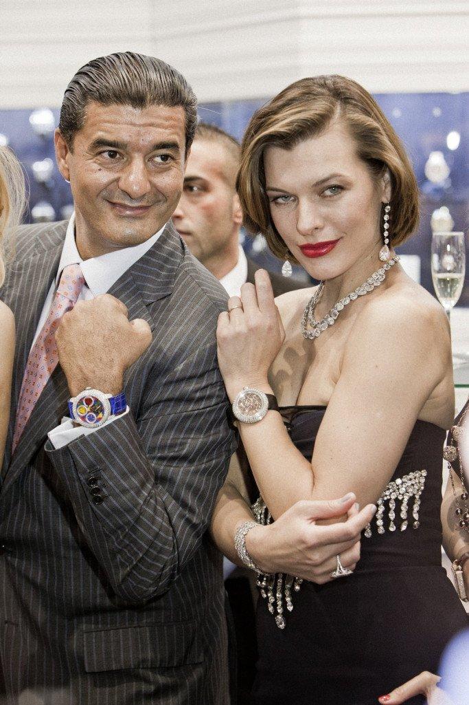 ג'ייקוב ארבו לצד מילה ג'ובוביץ' עם תכשיטים ושעונים שלו. מקור - בלוג JacobTheJewler.