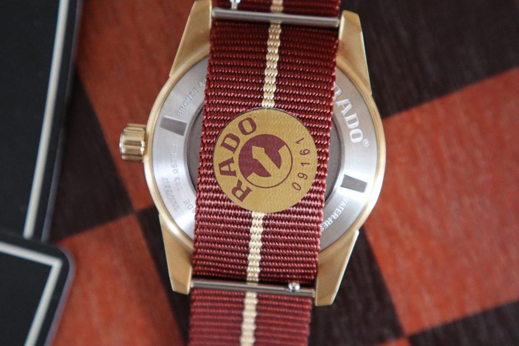 רצועת בד אדומה עם פס זהב והלוגו של ראדו. מקור - Hodinkee.